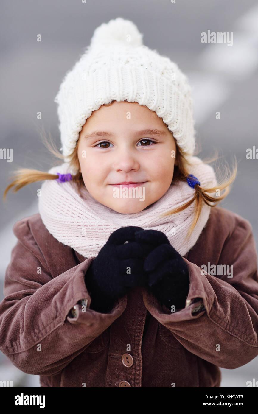 Retrato de un niño de una niña en un gorro blanco y una bufanda Imagen De 287247e6375
