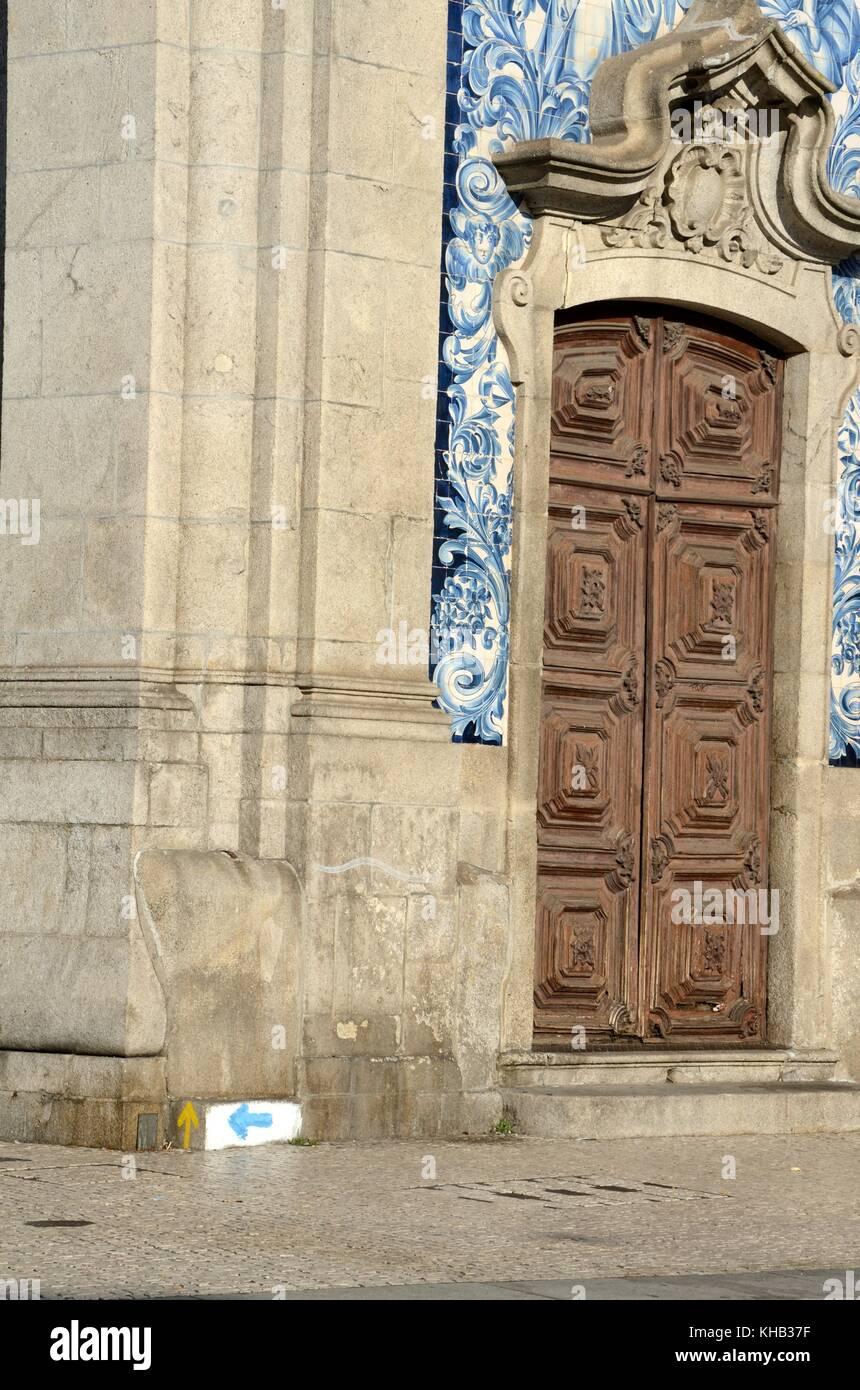 Puerta de madera adornados de Igreja do Carmo, Iglesia con la flecha azul indica el Camino Portugués y amarillo Foto de stock