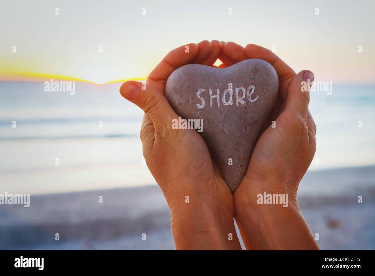 Compartir concepto, manos sosteniendo la piedra con palabra escrita en ella Imagen De Stock