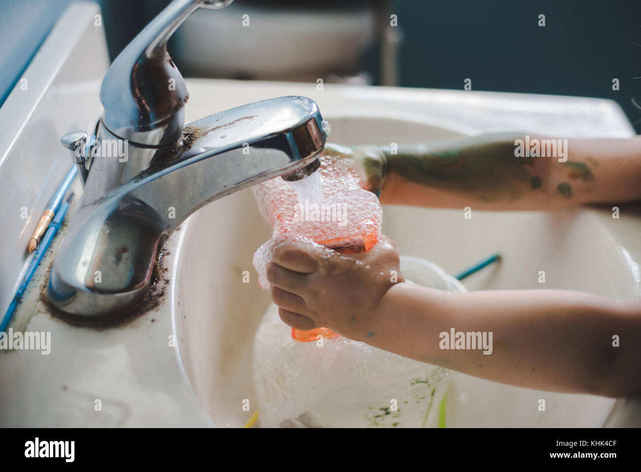Un niño niña pintura lavado las manos en un lavabo del baño. Imagen De Stock