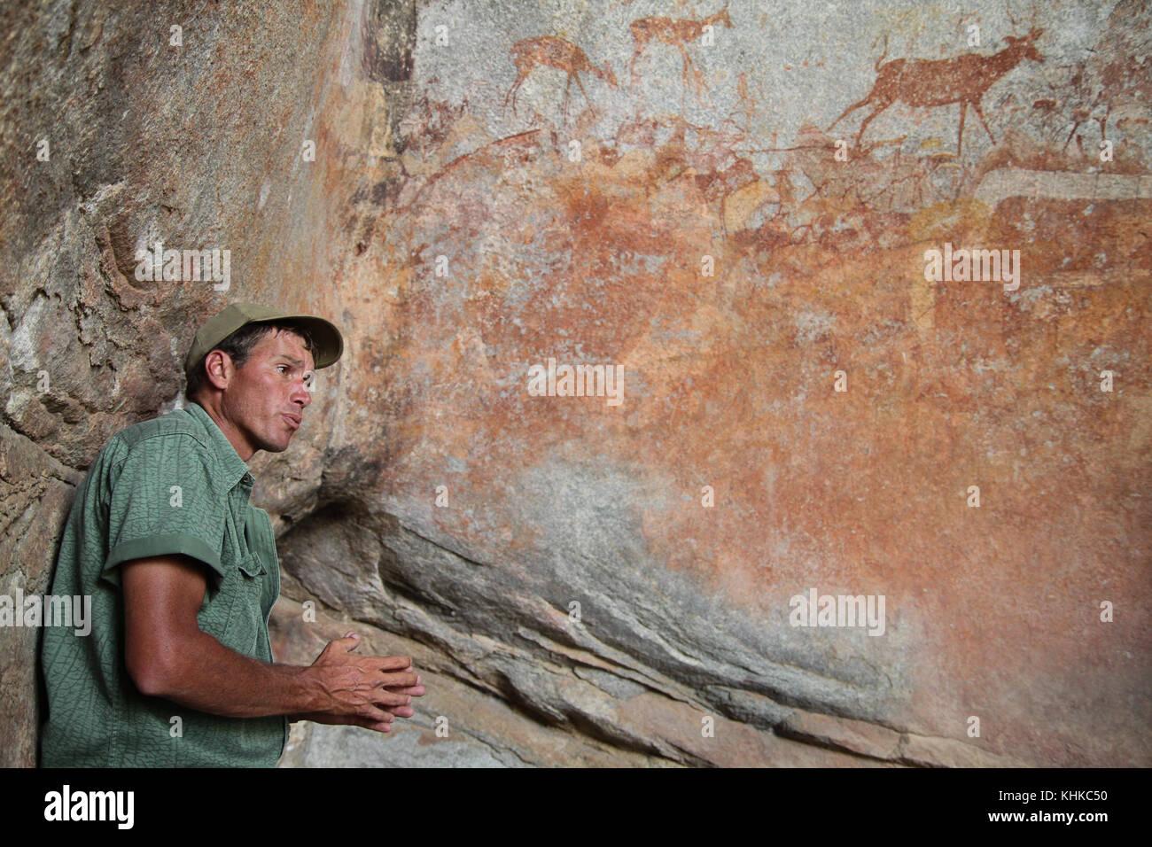 MATOPO, Zimbabwe, 17 de octubre. Guardabosque Ian Harmer conversaciones para turistas sobre pintura rupestre de Imagen De Stock