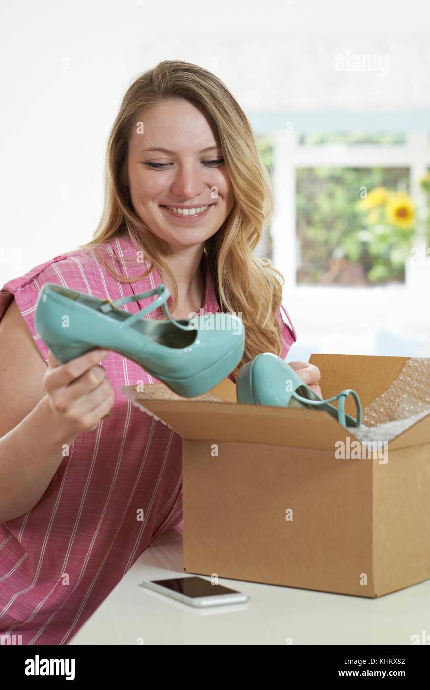 Mujer alegre y desembalaje de la compra online en casa Imagen De Stock