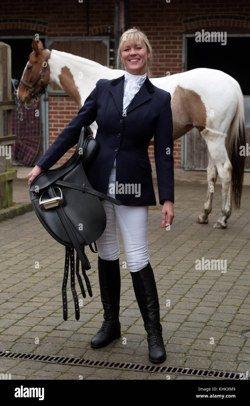 Atractiva mujer rubia sosteniendo una silla de cuero negro con su caballo skewbald stableyard. En noviembre de 2017. Imagen De Stock