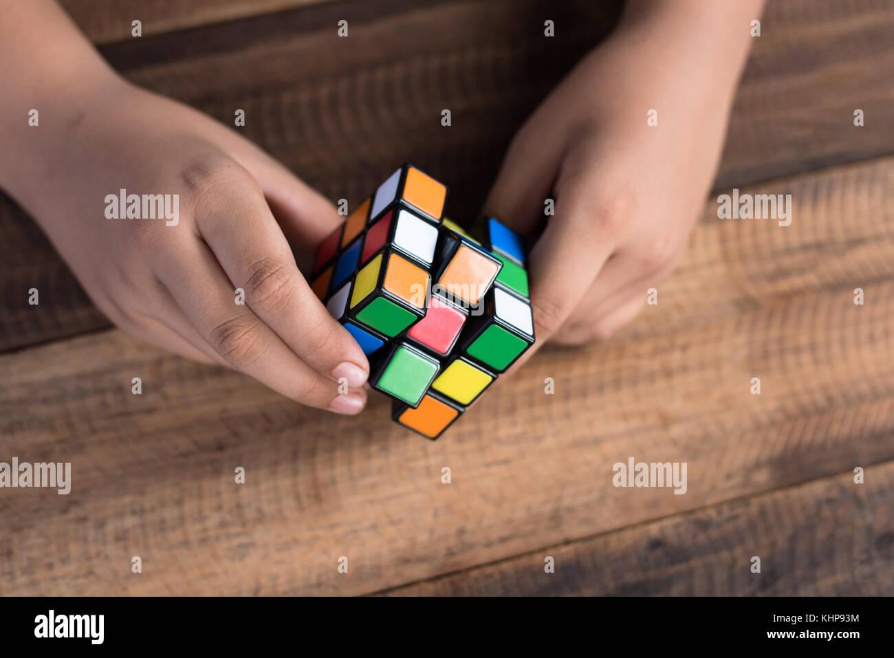 Chico asiático jugando con el cubo de Rubik.boy resolver rompecabezas.rompecabezas toy Imagen De Stock