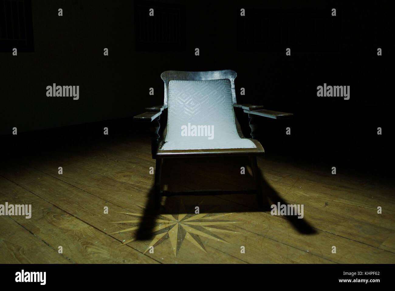 Una vieja silla de madera retro en el cuarto oscuro, la habitación ...