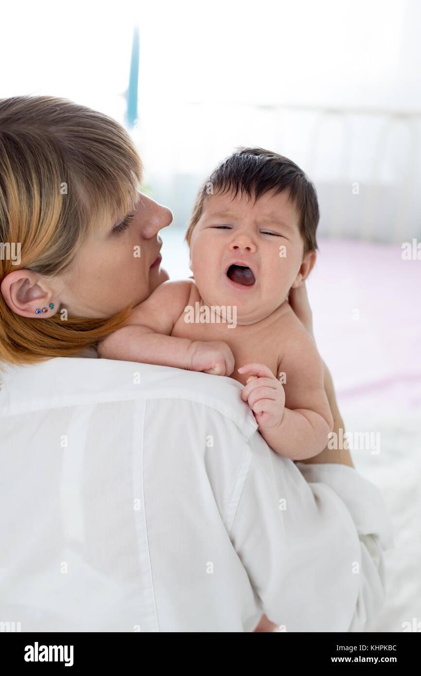 Madre está tratando de aliviar el llanto del bebé Imagen De Stock