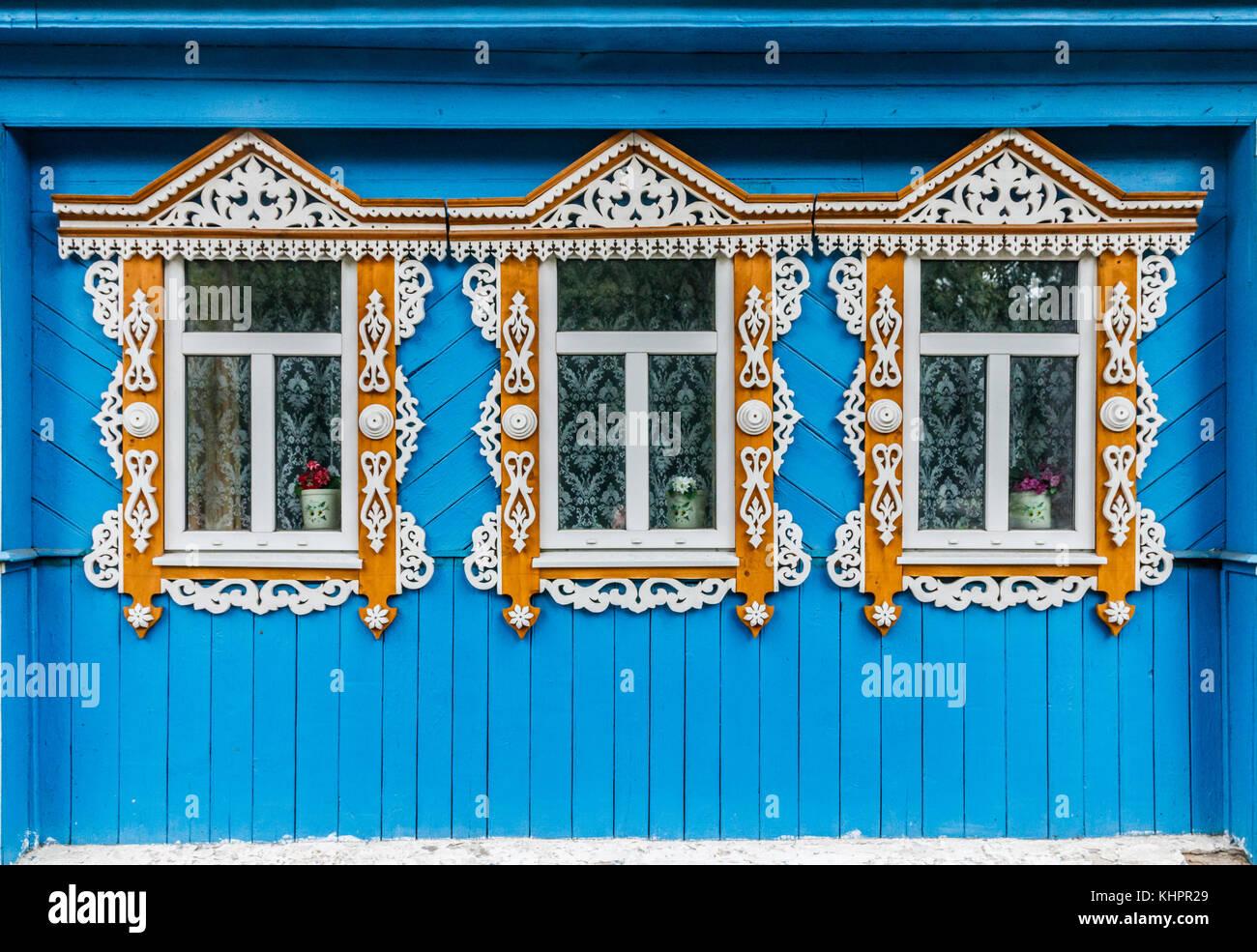 Tres ventanas en una pared de madera azul de una tradicional casa de ...