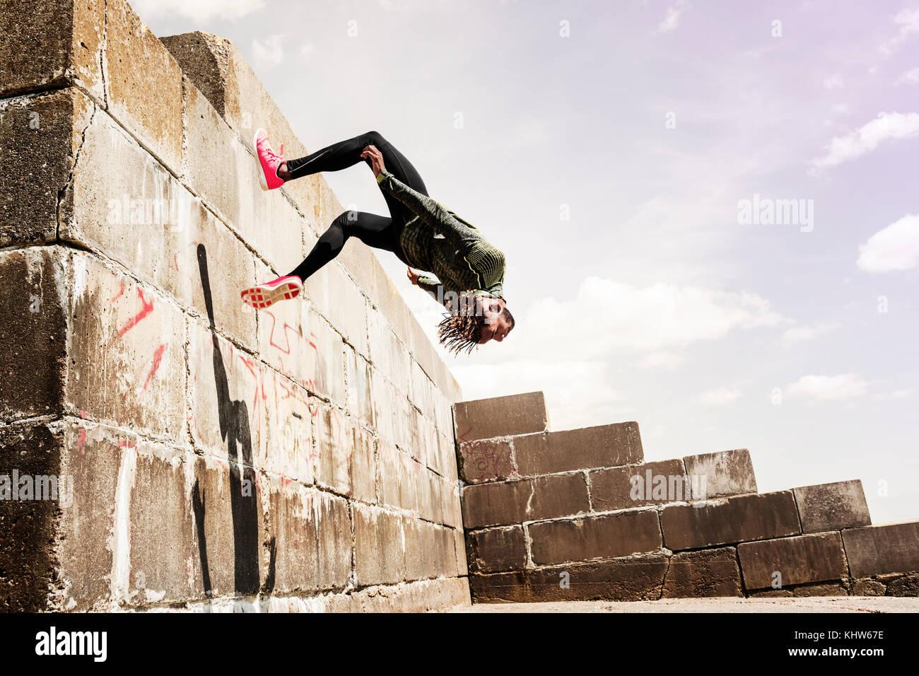 Joven, Free Running, al aire libre, somersaulting desde el lado de la pared Imagen De Stock