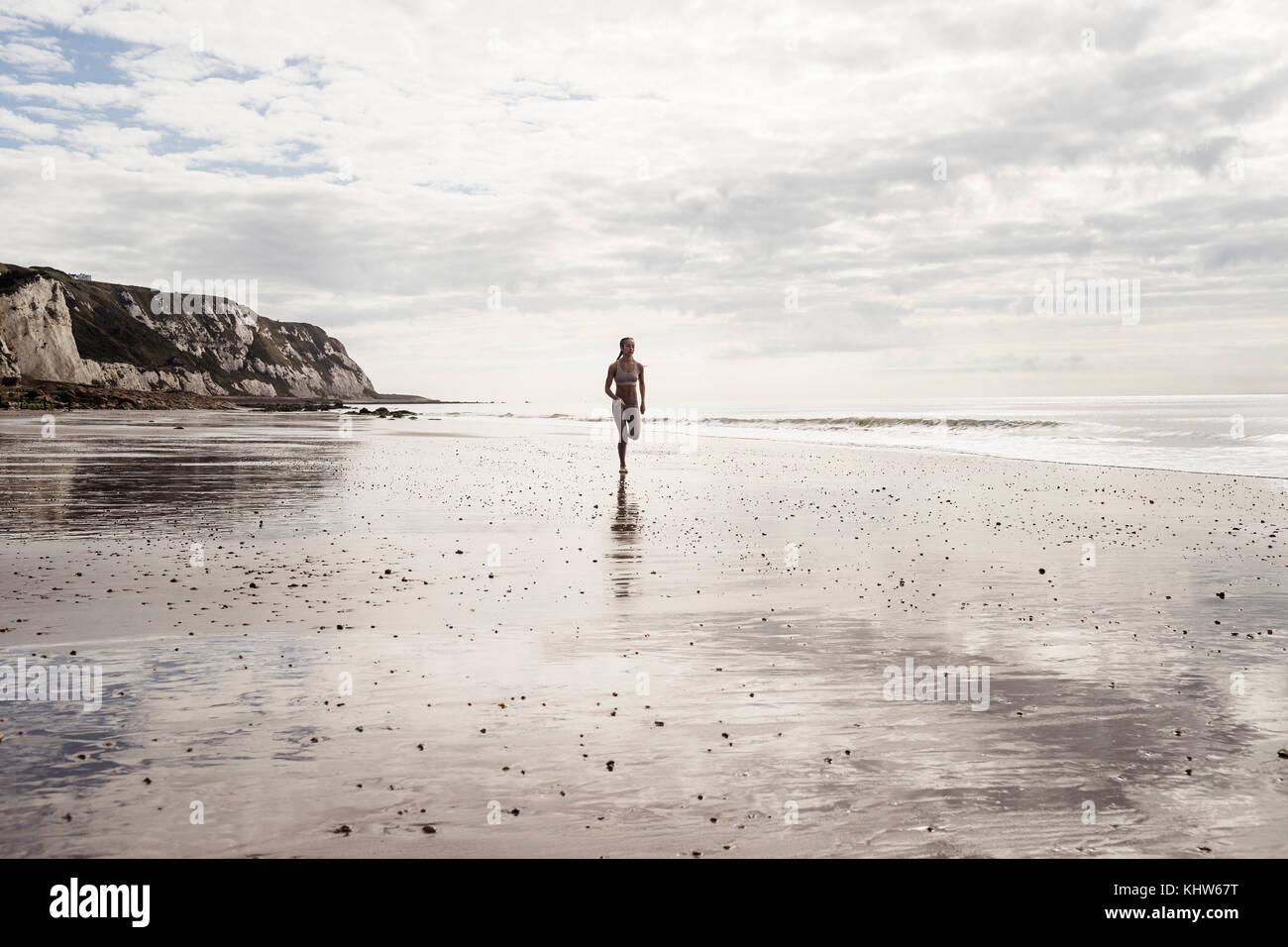 Mujer joven que corre a lo largo de playa Imagen De Stock