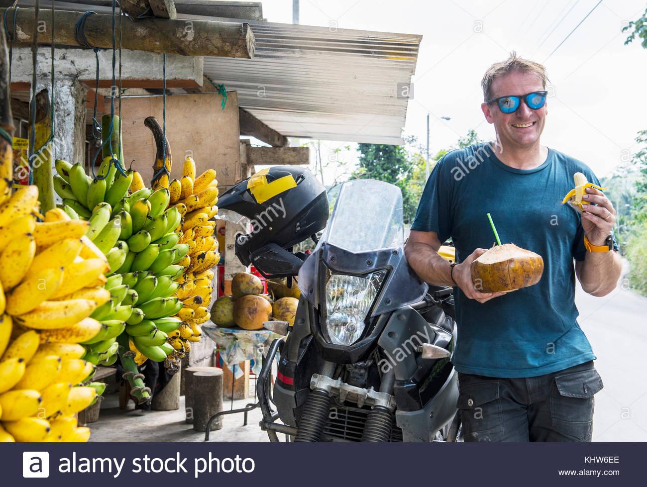 Moto rider disfruta de fruta local, Machala, el oro, Ecuador, Sudamérica Imagen De Stock