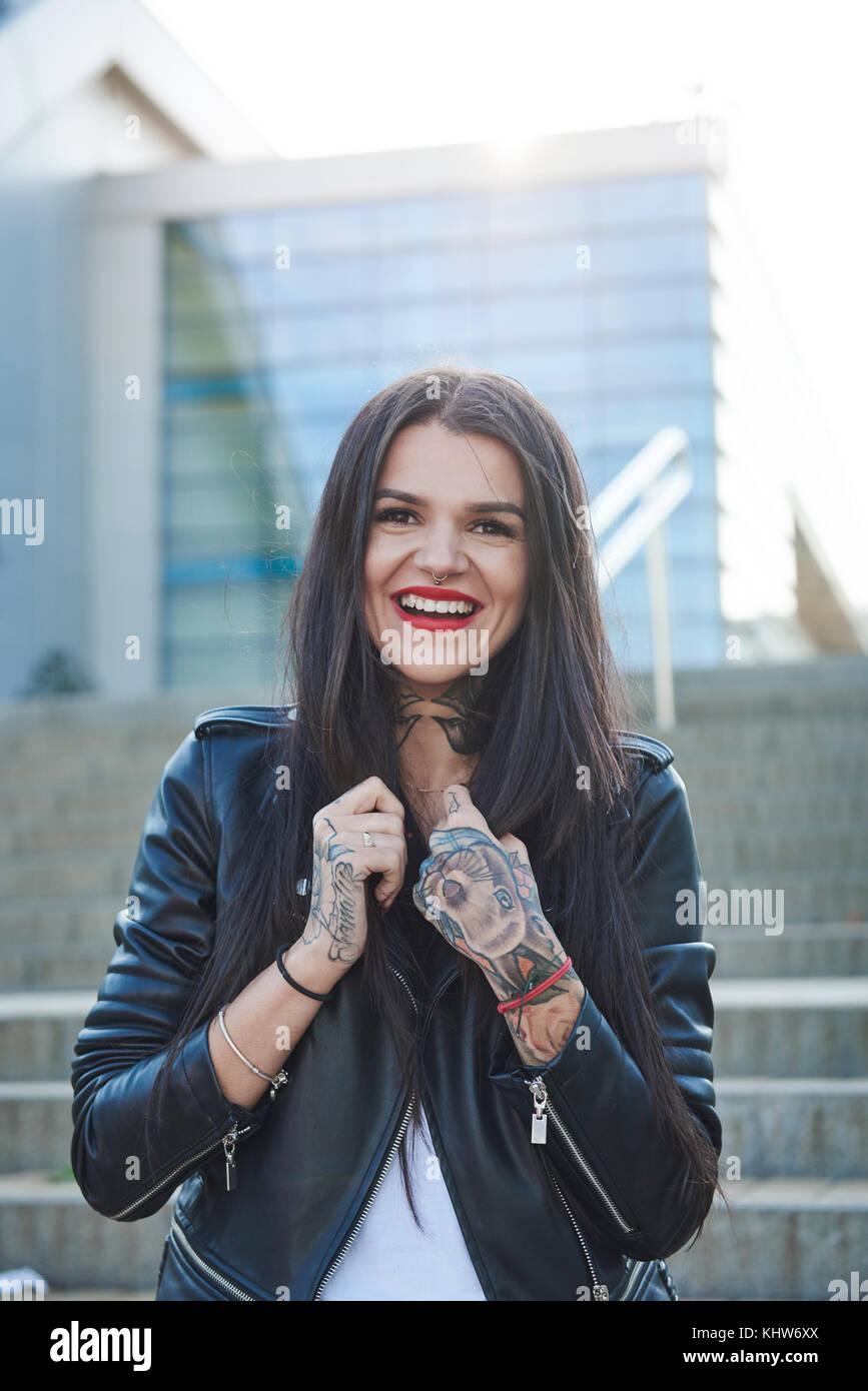 Retrato de mujer joven celebración collares de chaqueta, sonriendo, tatuajes en las manos Foto de stock