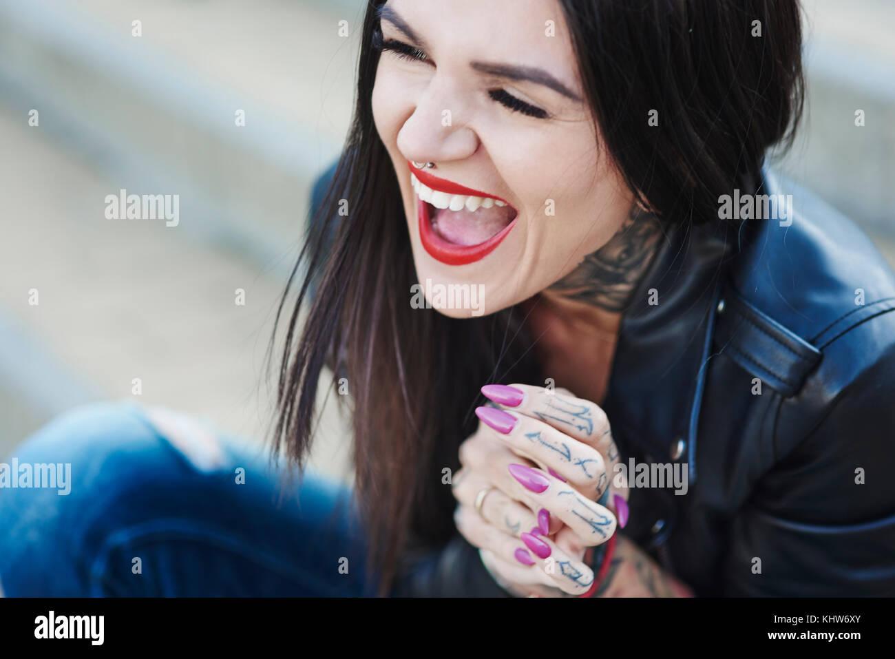 Retrato de mujer joven riendo, tatuajes en el cuello y la mano Imagen De Stock