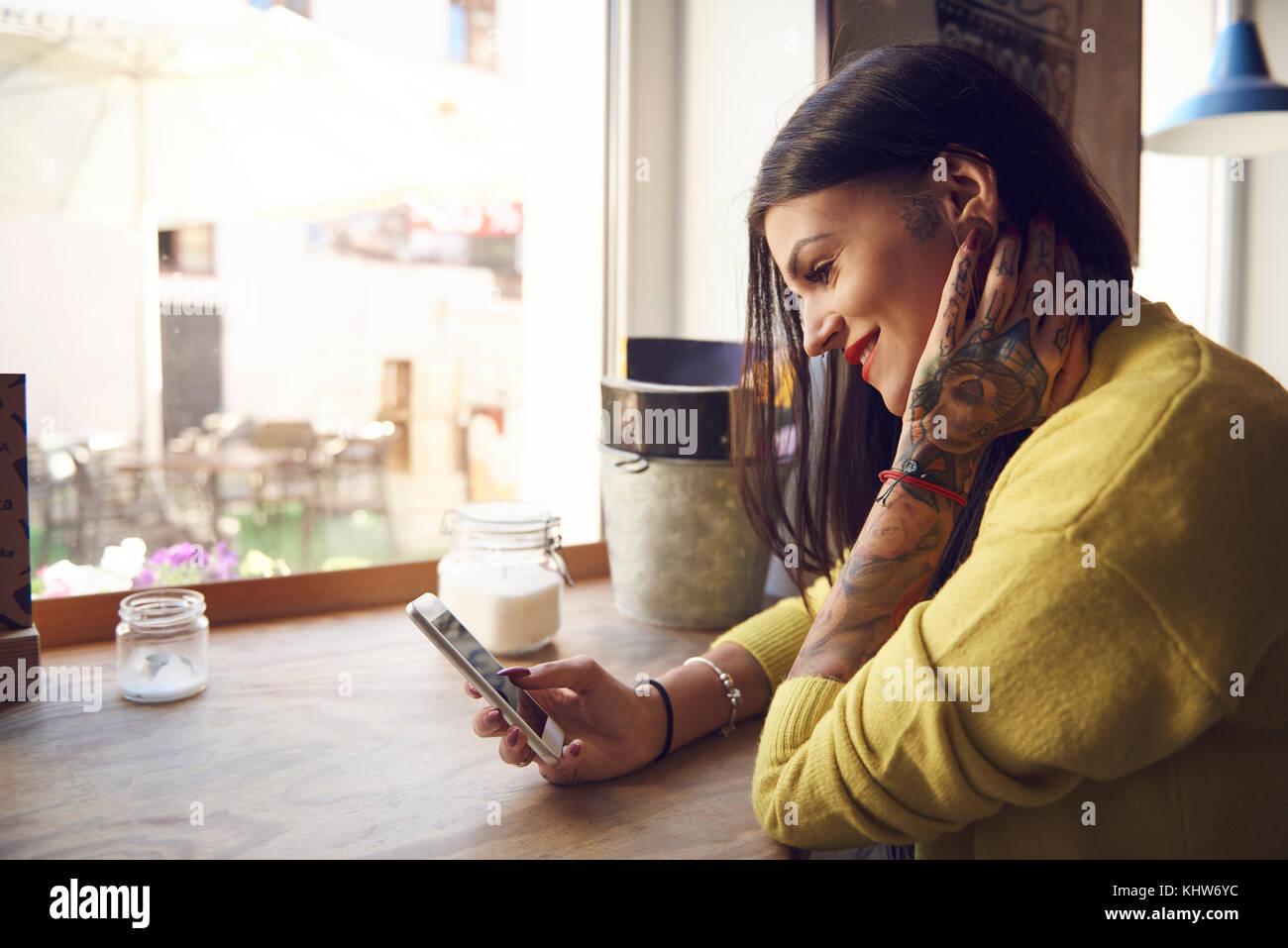 Mujer joven sentado en la cafetería, con smartphone, tatuajes en el brazo y mano Imagen De Stock