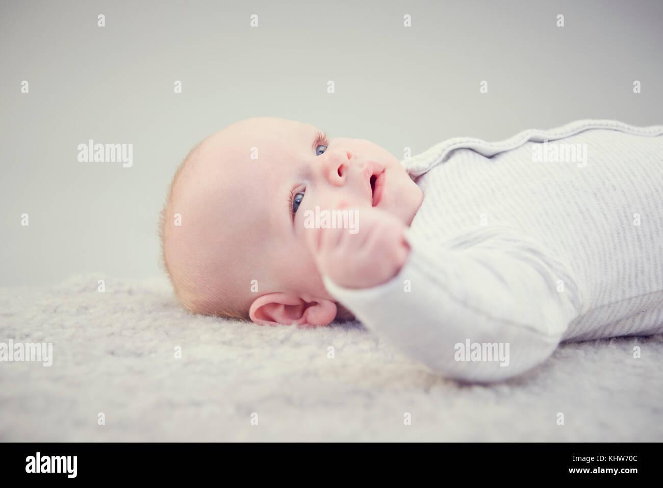 Bebé recién nacido, acostado sobre una alfombra de cerca Foto de stock