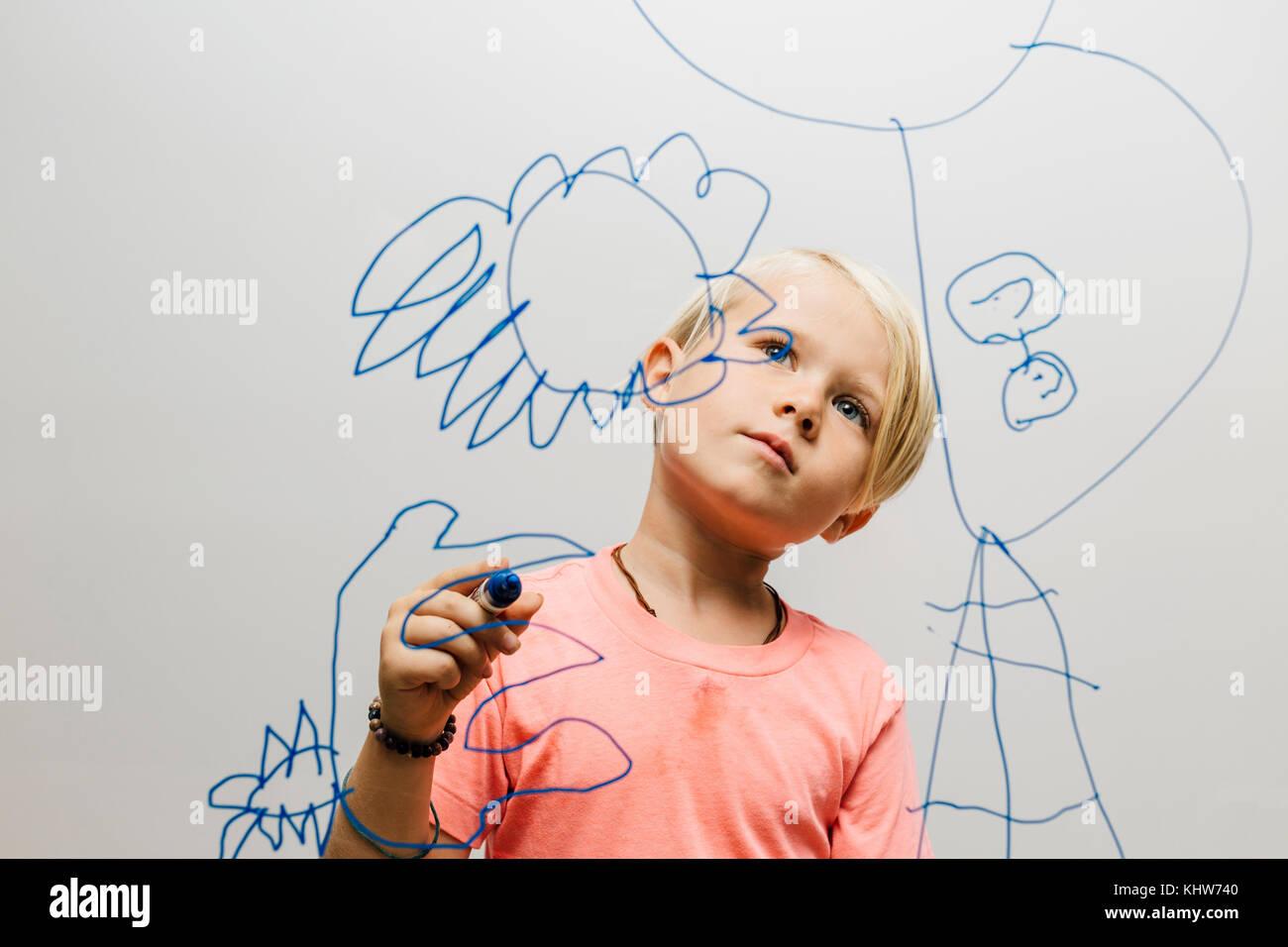 Boy admirando su lápiz marcador dibujo en pared de vidrio Foto de stock