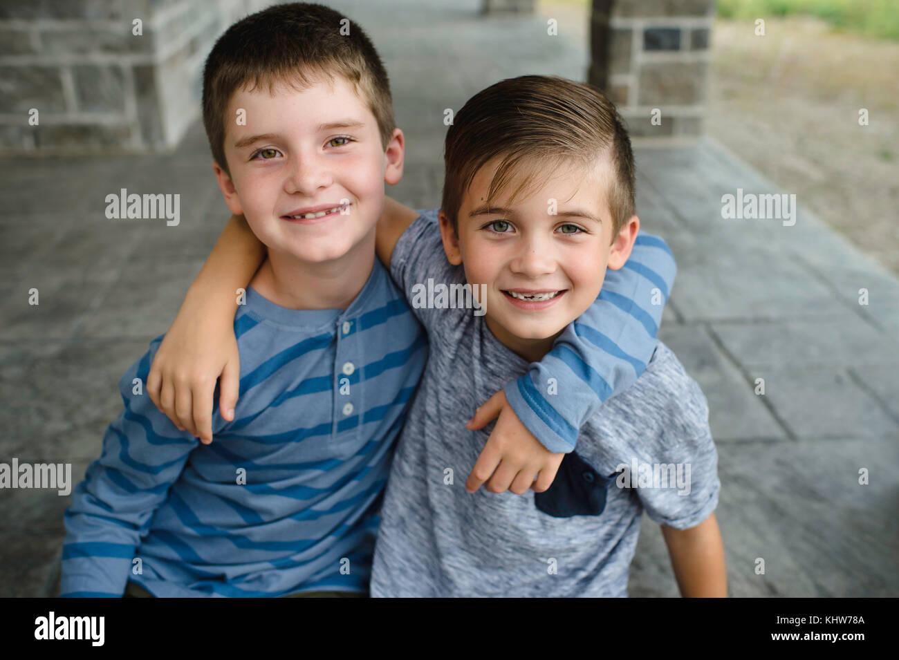 Los hermanos, con los brazos alrededor de cada una de las otras Foto de stock