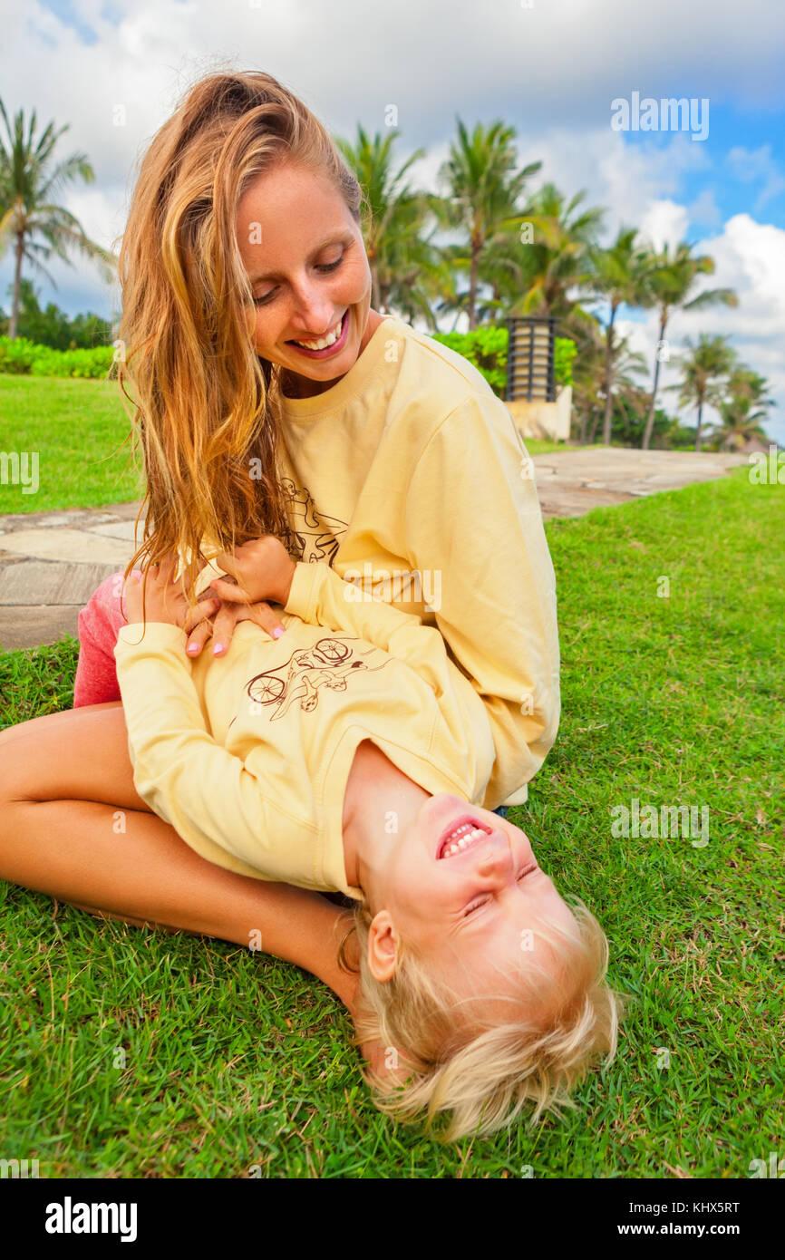 Familia feliz sobre la hierba verde. Los niños se divierten en el exterior a pie - madre cosquilleo Gracioso bebe Foto de stock