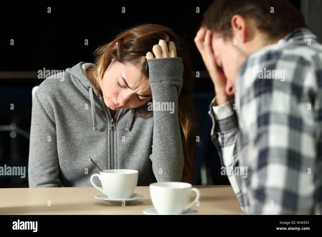 Triste pareja de adolescentes quejarse sentado en un bar en la noche Imagen De Stock