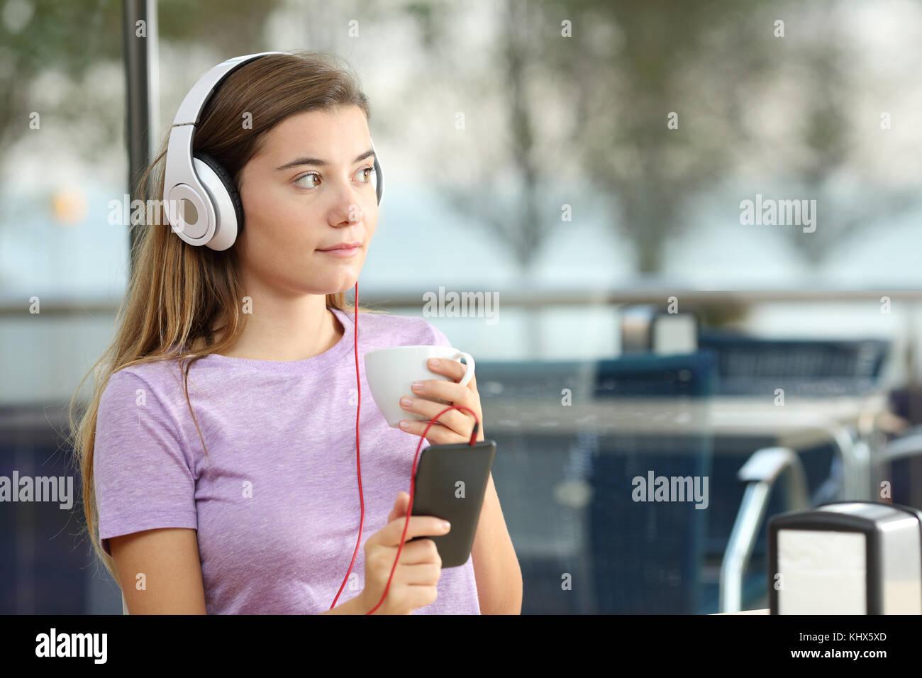 Adolescente grave escuchando música sosteniendo una taza de café y un teléfono inteligente en un Imagen De Stock