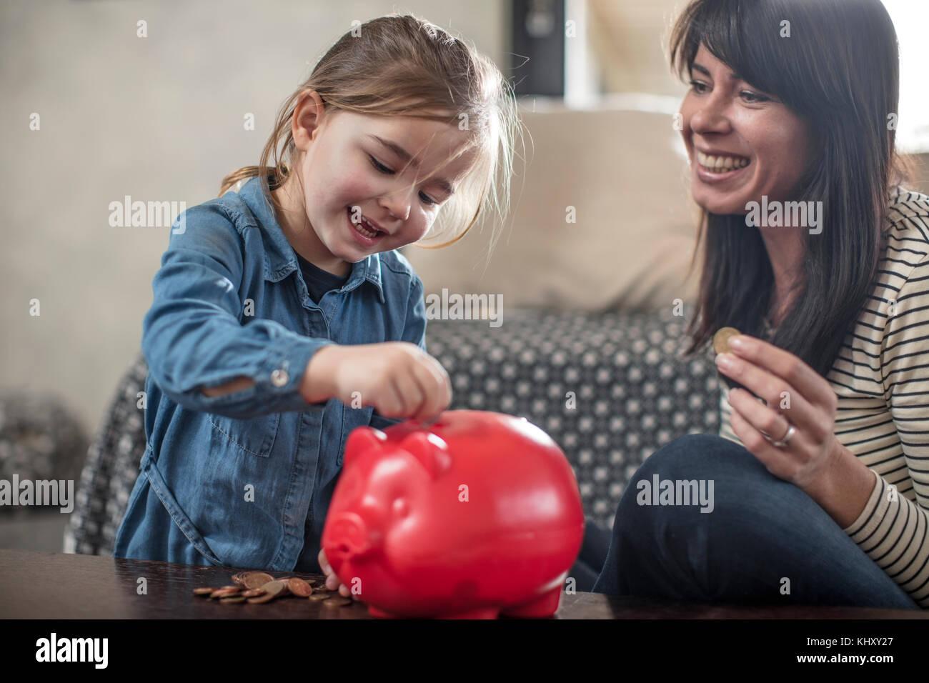 Chica insertando una moneda de madre en rojo hucha en mesa de café Foto de stock