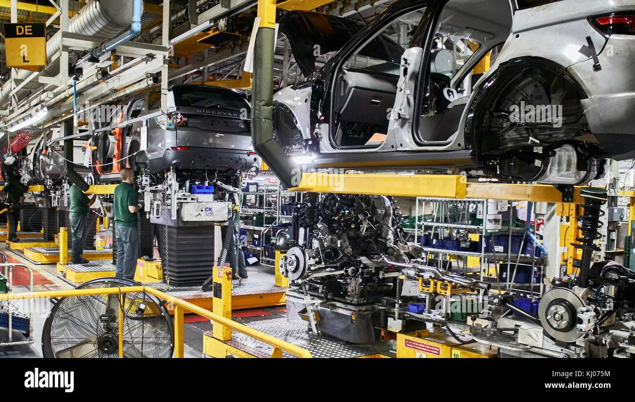 Los trabajadores sobre el motor en la línea de producción en la fábrica de coches Imagen De Stock