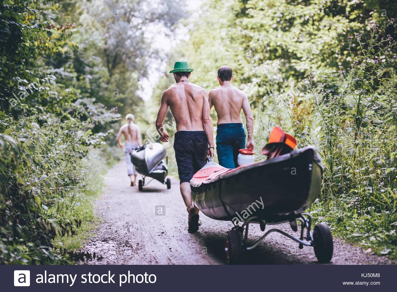 Hombres que llevaban su kayak por el bosque Imagen De Stock