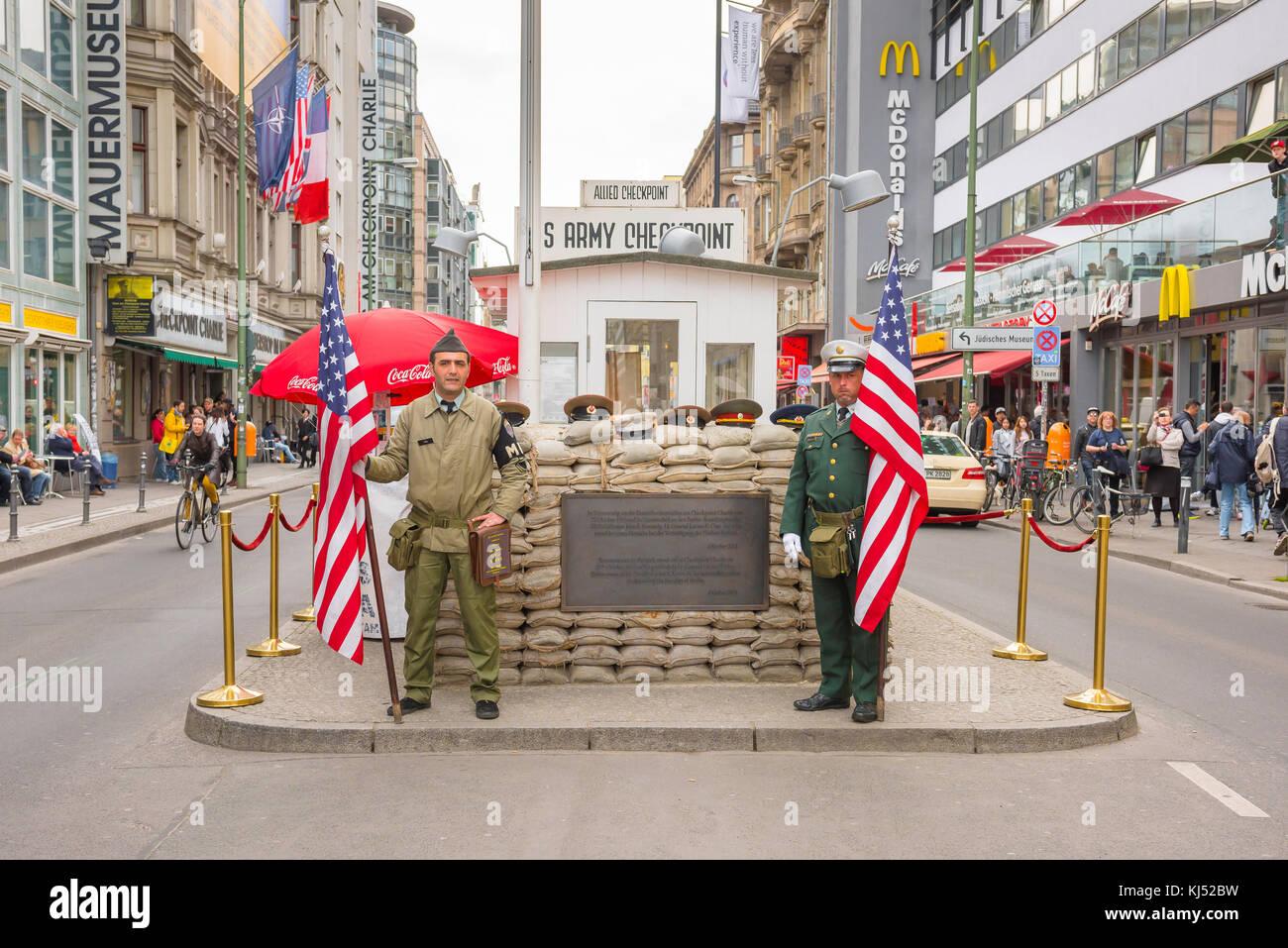 Checkpoint Charlie Berlín, dos hombres sosteniendo banderas americanas volver a promulgar las funciones de Imagen De Stock