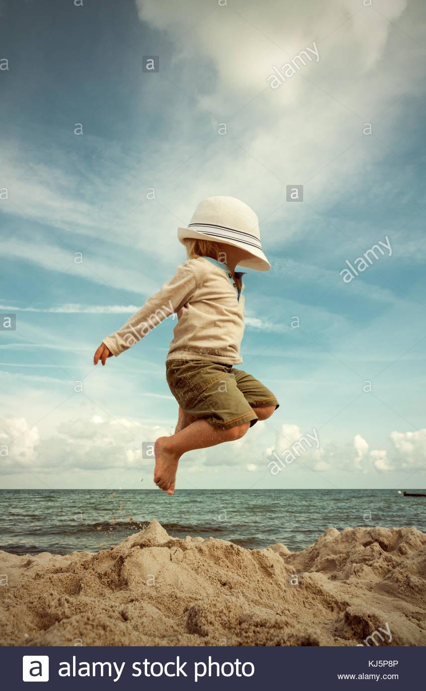 Chico saltando en la playa con un sombrero que cubre su rostro Imagen De Stock