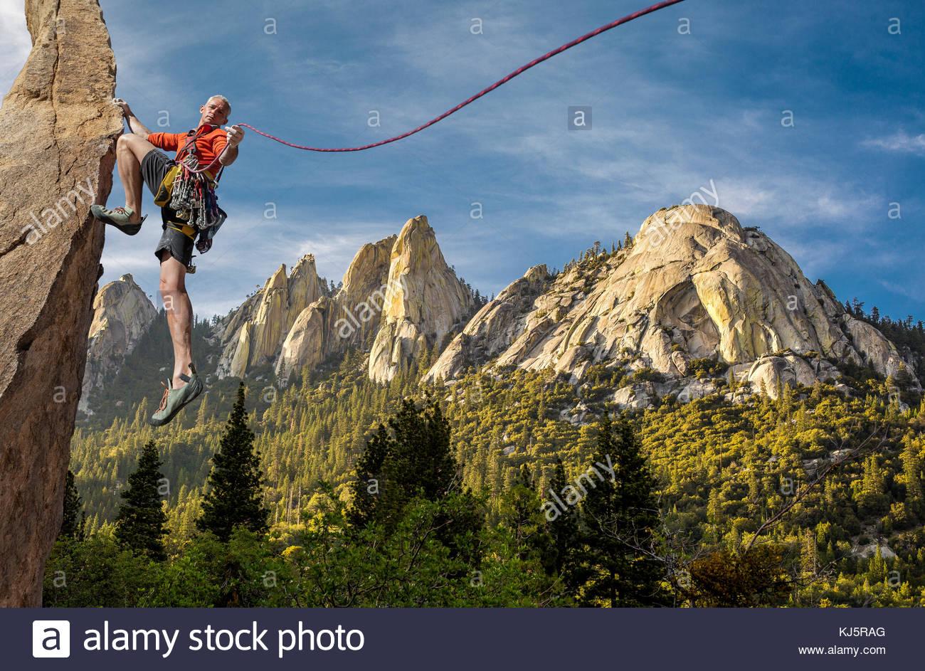 Escalador sosteniendo un hermoso paisaje de montaña de la cuerda. Imagen De Stock