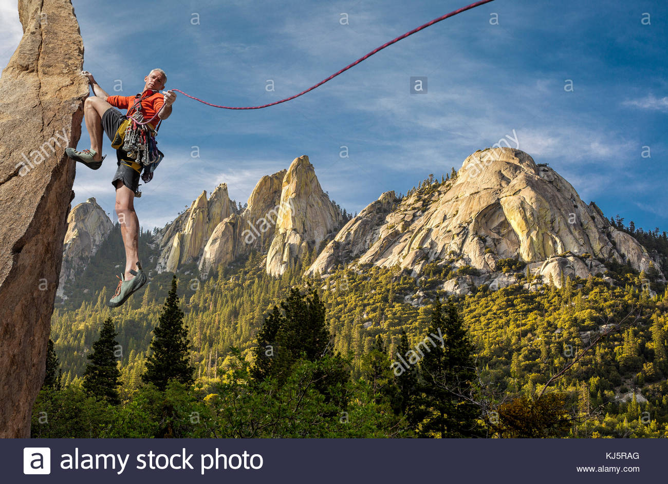Escalador sosteniendo una cuerda. Hermoso paisaje de montaña Imagen De Stock
