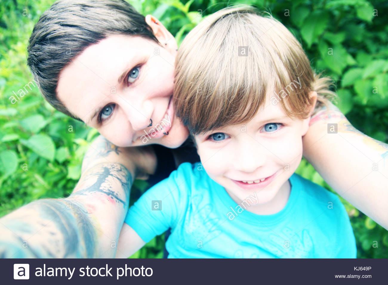 Madre e hijo de ojos azules sonriendo mientras toma un selfie Imagen De Stock