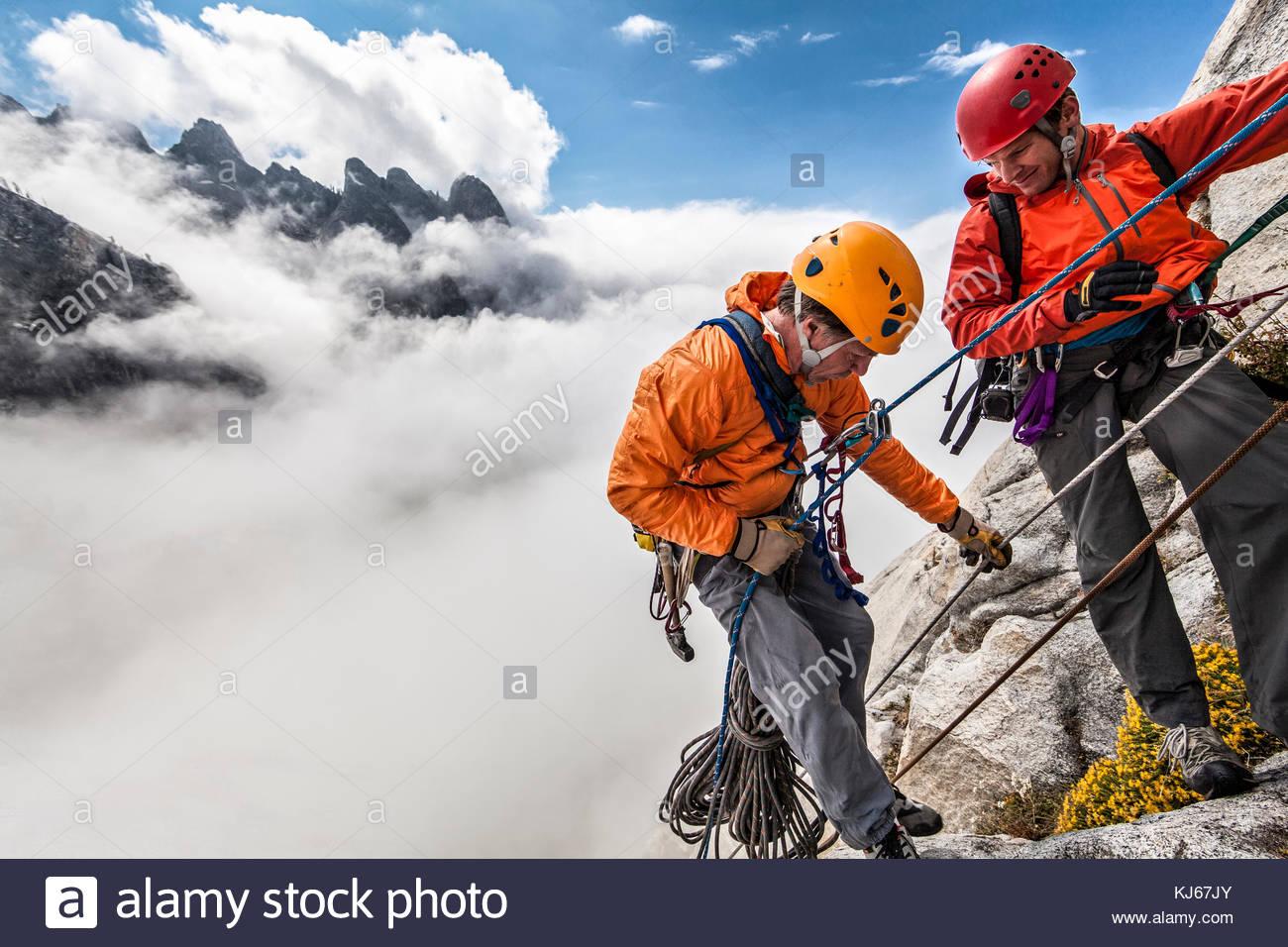 Los escaladores tratando de alcanzar la cima, nublado picos antecedentes Imagen De Stock