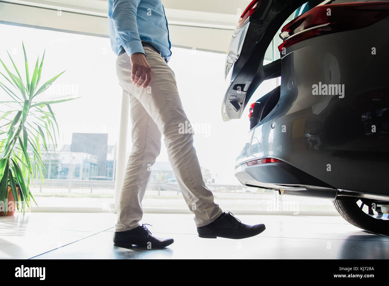 Cerca del macho adulto piernas abriendo la puerta de un automóvil con el movimiento de las piernas, sin tener que utilizar la llave del auto, tomadas en interiores en el concesionario de coches Foto de stock