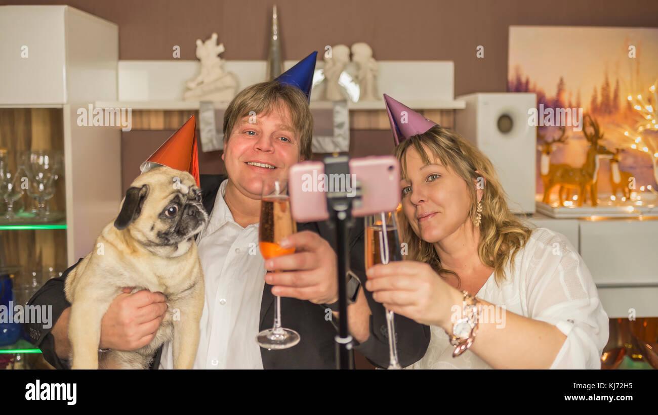 Pareja de mediana edad hace con sus pug un selfie durante una fiesta de Nochevieja en casa Imagen De Stock