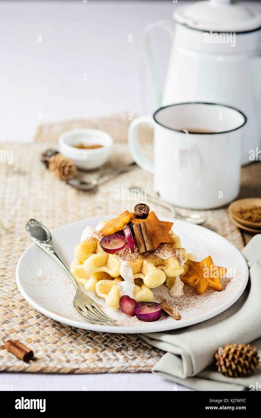 Mesa de desayuno: waffle con frutas frescas, canela y yogur. Vista frontal del tiempo de Navidad. Imagen De Stock