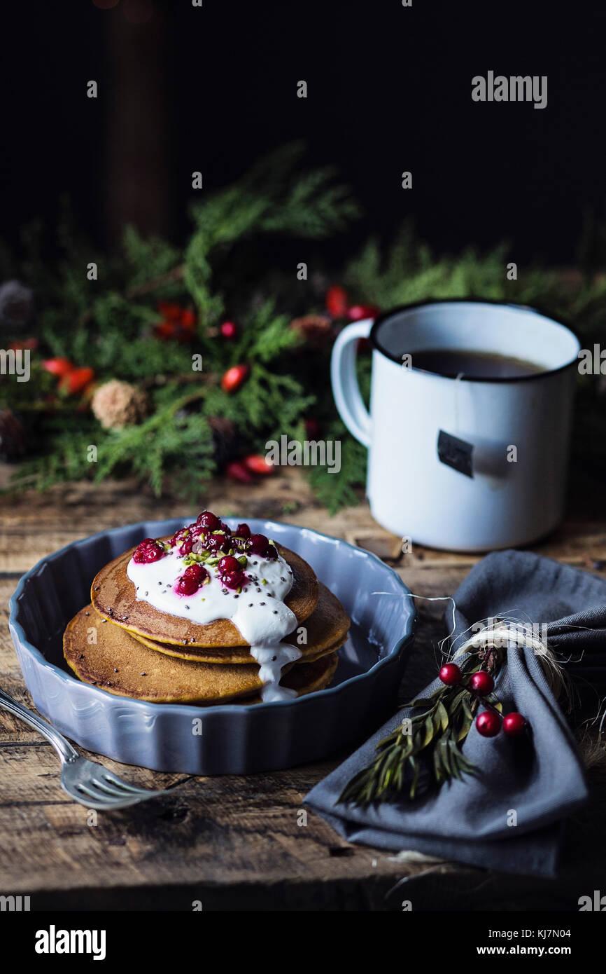 Mesa de desayuno de Navidad: calabaza crepes con crema de yogur y grosella Imagen De Stock