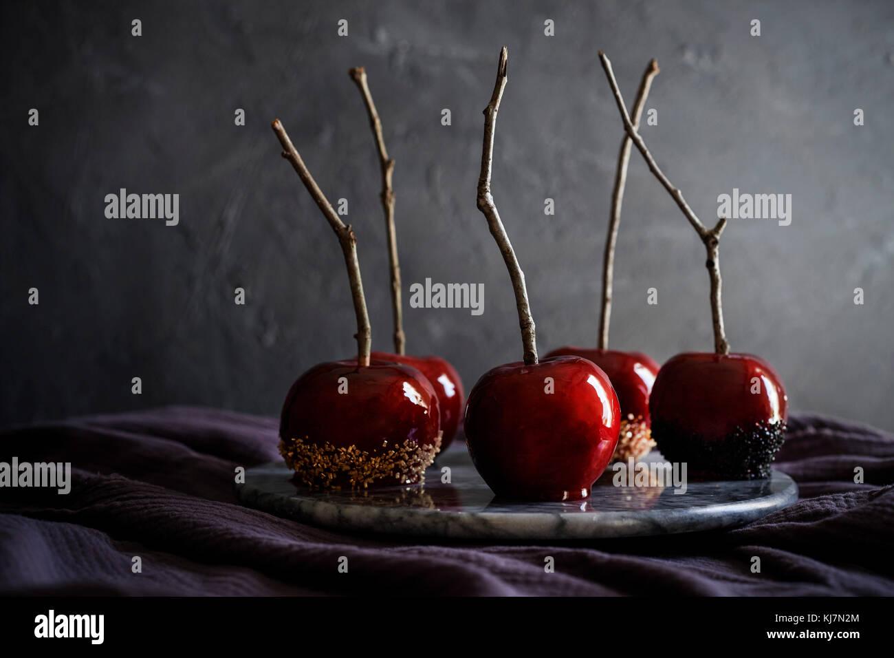 Bandeja de mármol precioso, rojo, manzanas de caramelo en lino de color púrpura oscuro. Moody sentir con oscuro fondo de textura. Foto de stock