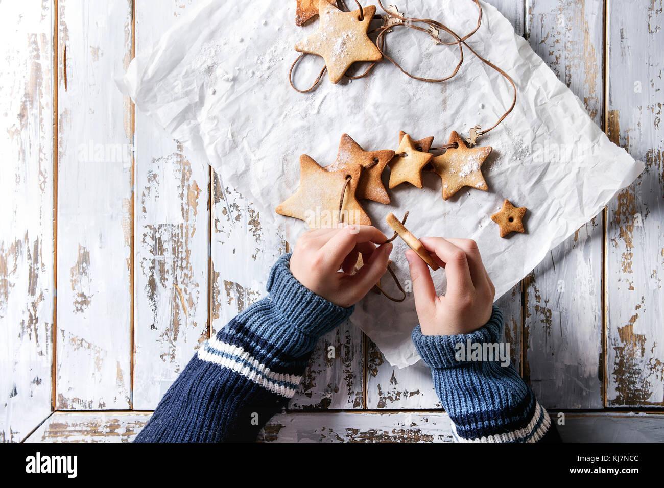 Niño manos hacen guirnalda de galletas caseras galletas de azúcar en forma de estrella en el subproceso Imagen De Stock