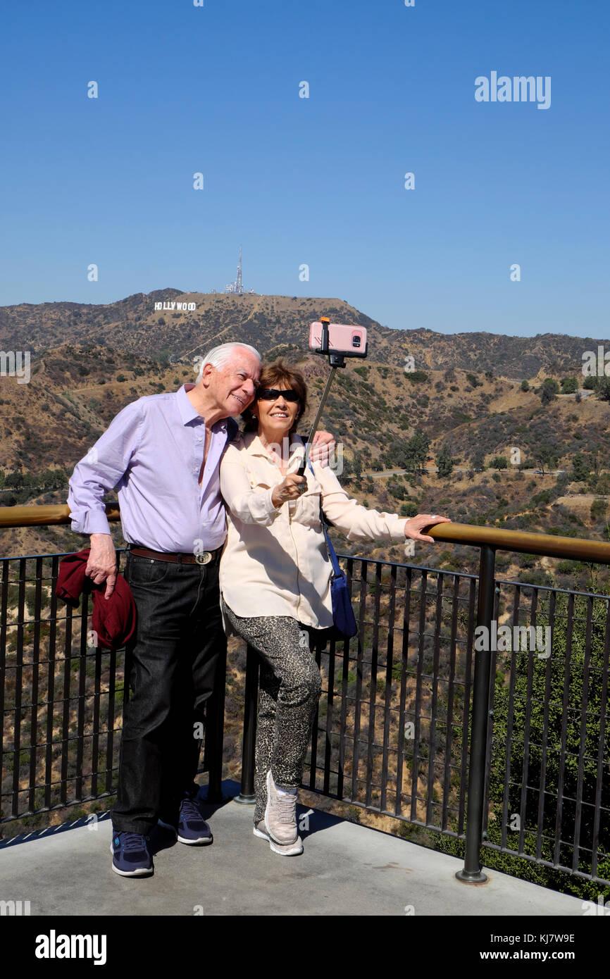 Las parejas ancianas teniendo selfie fotografía con teléfono celular en la parte delantera de Hollywood Imagen De Stock