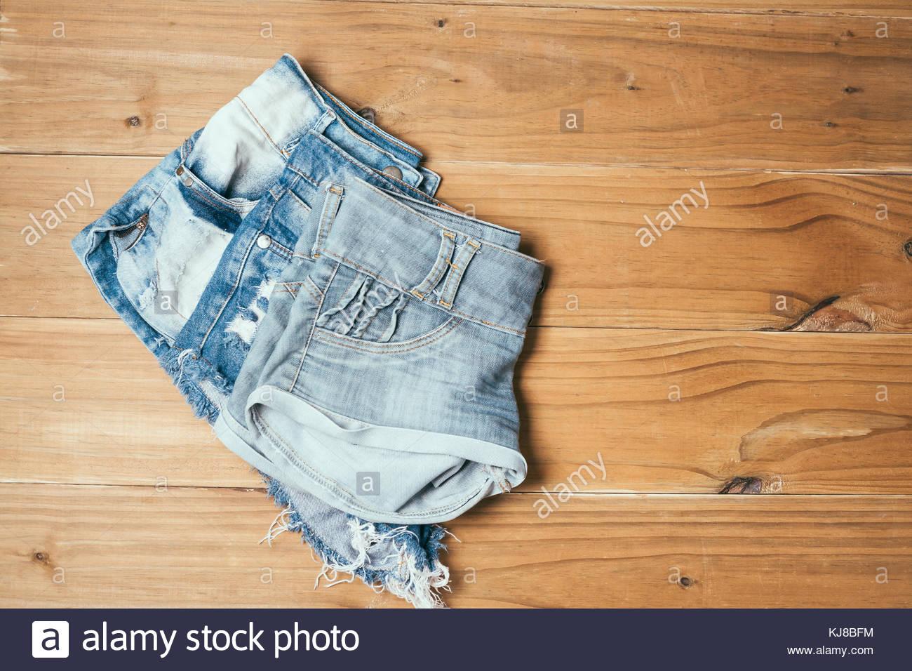 063411ec1f Hembra shorts pantalones vaqueros rasgados azul sobre fondo antiguo de  madera Imagen De Stock
