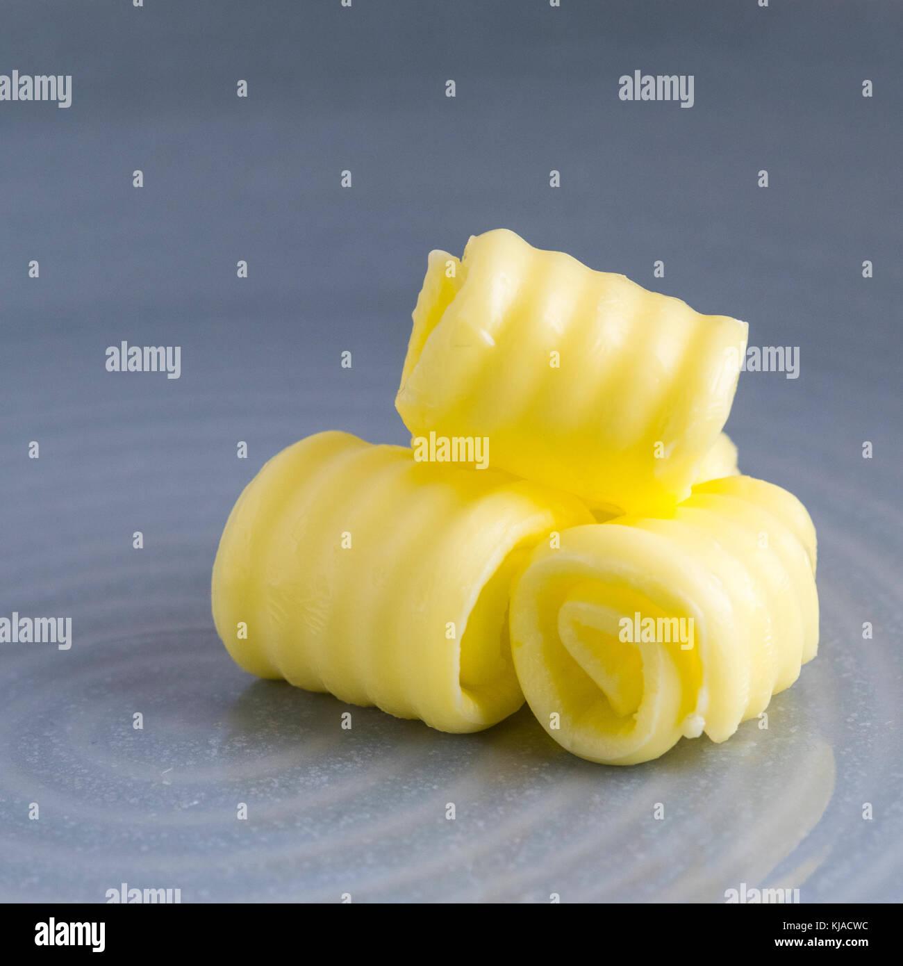 Imagen cuadrada de mantequilla orgánica fresca curvado en una placa con espacio para texto superpuesto y un Imagen De Stock
