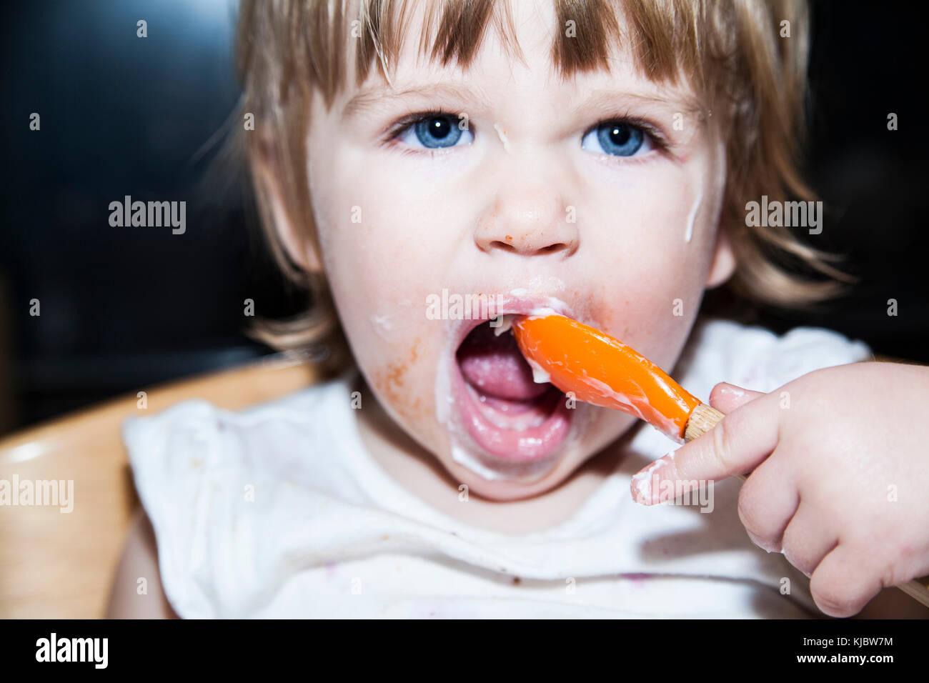 Niño desordenado de comer con una cuchara Imagen De Stock