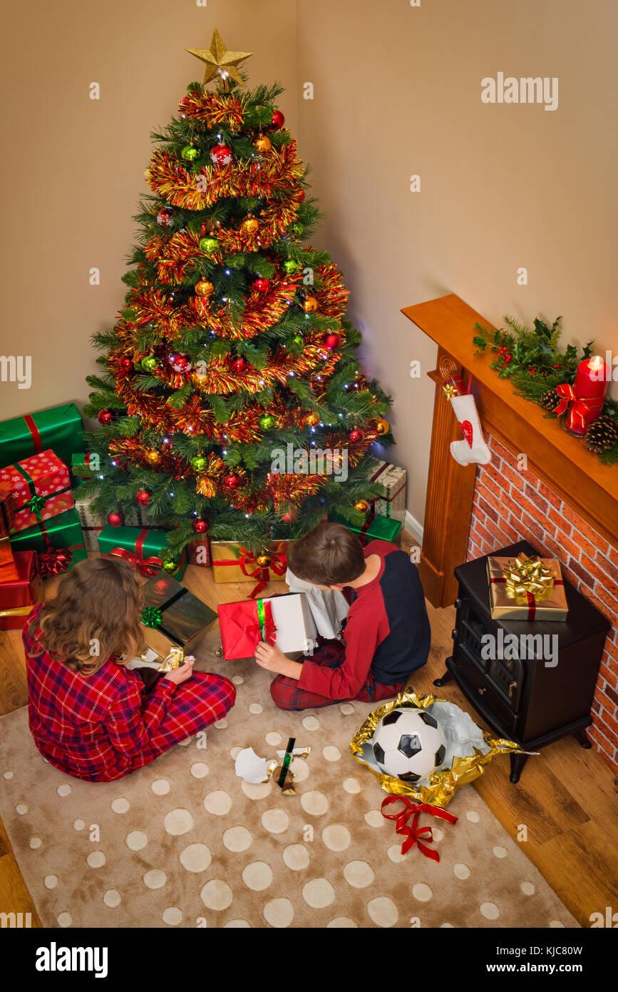 Vista aérea de niños abriendo sus regalos regalos envueltos en la mañana de Navidad sentado junto Imagen De Stock