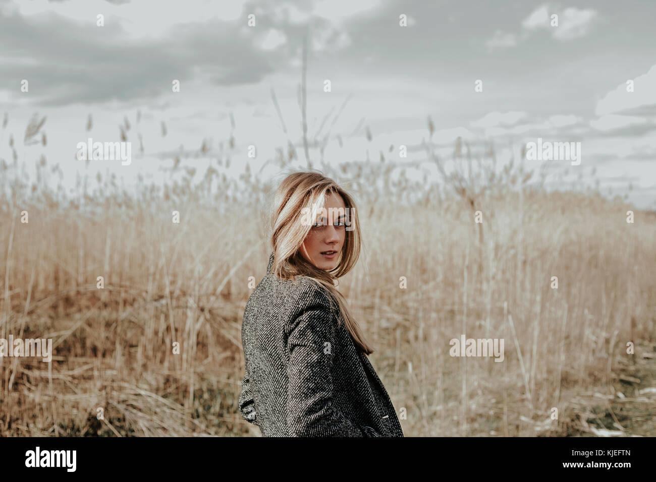 Bonita y joven con largo cabello rubio vestida de abrigo de lana mirando a la cámara a través de su hombro Imagen De Stock
