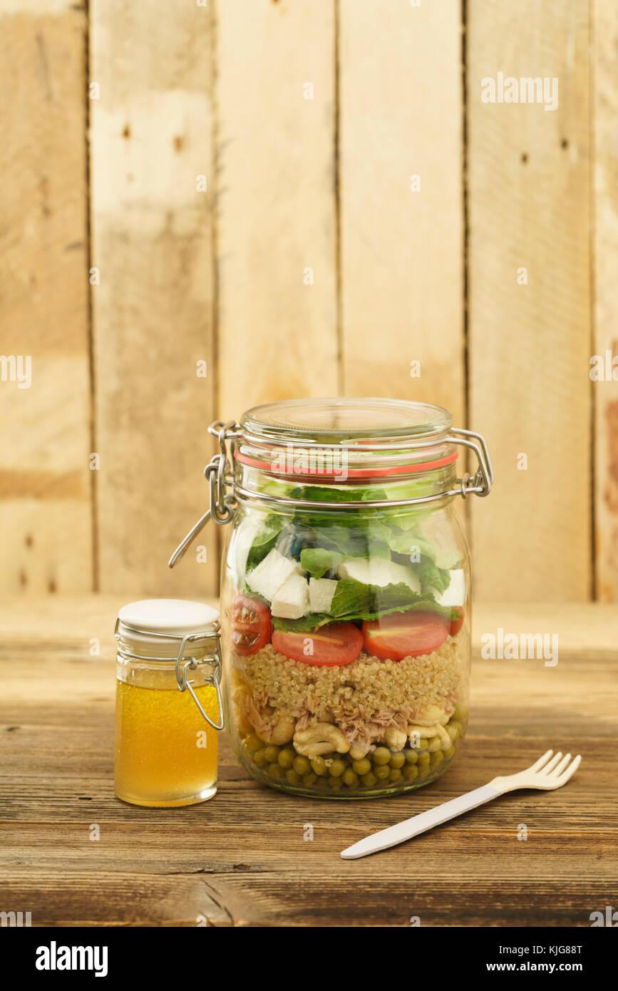 Salat zum Mitnehmen Glas im mit Erbsen, Cashew-Nüssen, Thunfisch, cuscús, Cocktailtomaten, Minze, Schafskäse, Blattsalat Foto de stock
