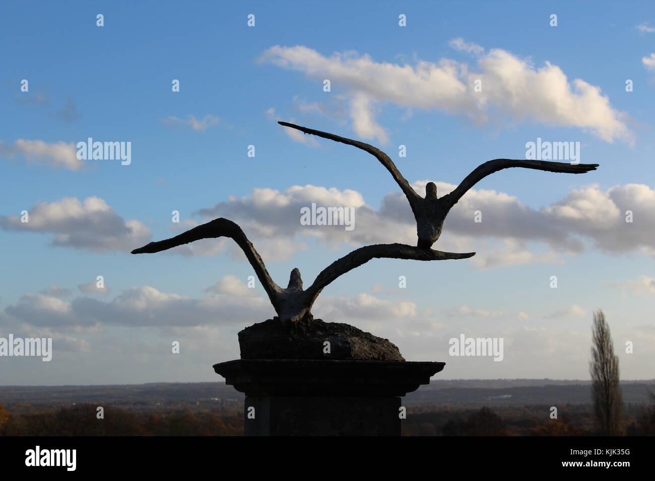 Pájaros en vuelo estatua mirando el paisaje Foto de stock
