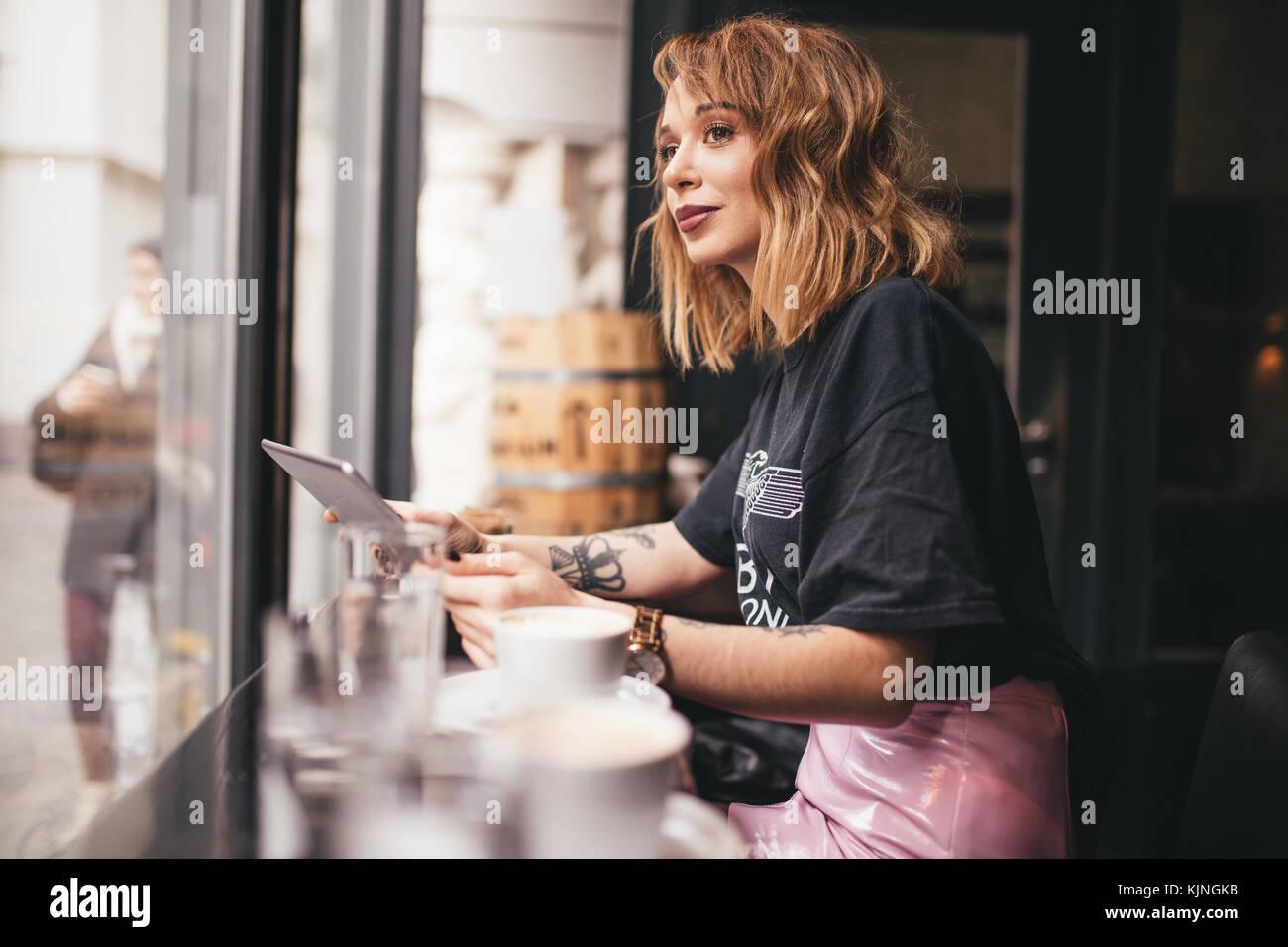 Bonita chica sonriente y mirando por una ventana de barra Imagen De Stock
