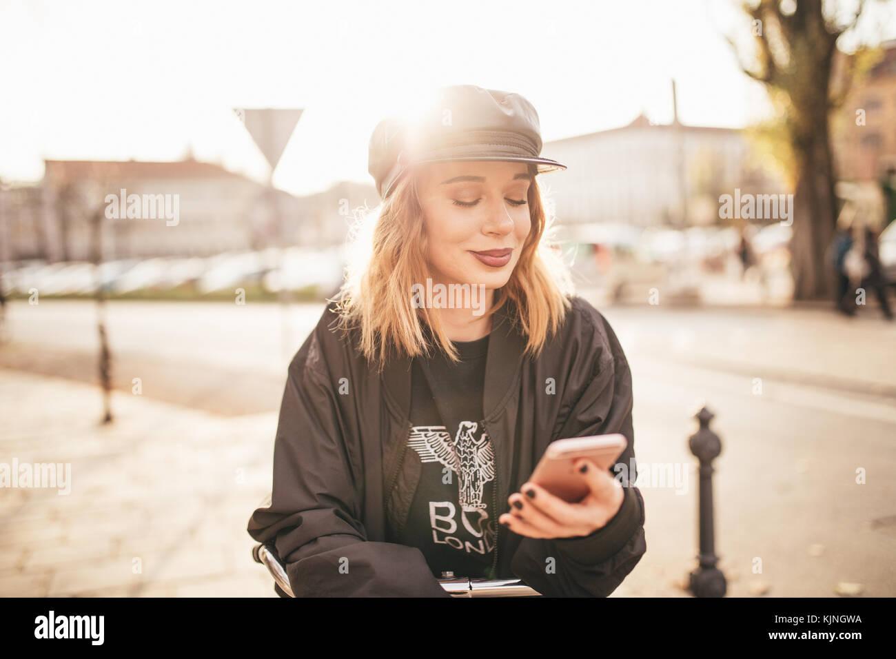 Hermosa niña escribir mensajes de texto en su celular en las calles de la ciudad Imagen De Stock