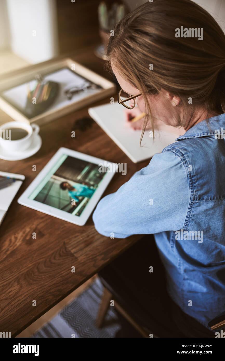 Mujer joven sentada sola en una mesa trabajando con una tableta digital y escribir las ideas en un bloc de notas Foto de stock