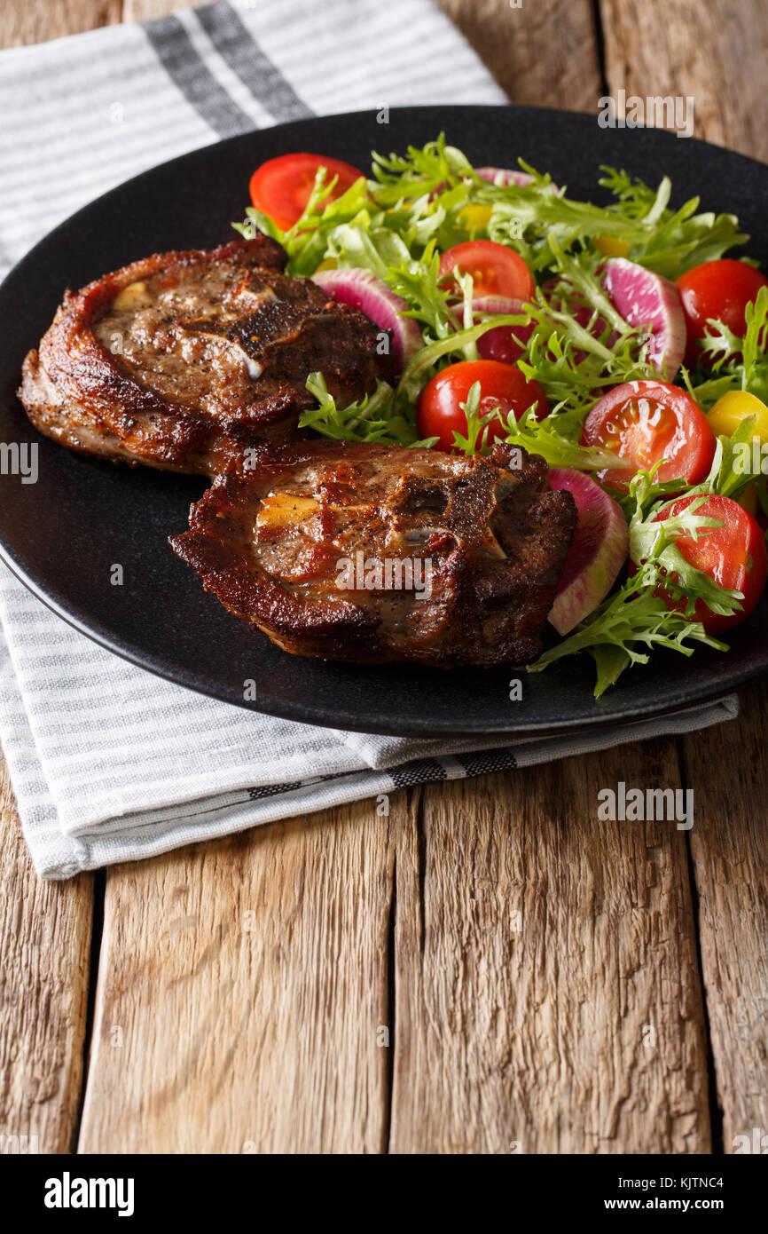 Delicioso filete de cordero y ensalada de verduras de rábanos, tomates y lechuga cerca en una placa vertical. Foto de stock